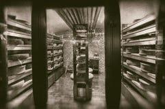 Stora hjul av ost som mognar i magasinmejerikällaren - retro fotografi royaltyfria foton