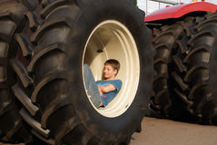 Stora hjul av traktoren med en pojke inom Royaltyfri Foto