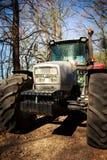 Stora hjul för Closeuptraktorhätta på jordvägen i vårskog Arkivbilder