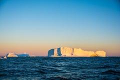 Stora isberg i soluppgång Grönland sikt arkivfoton