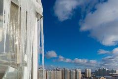 Stora istappar hänger på balkong av ett hus i stad Arkivbild