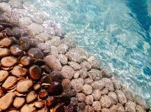 Stora kiselstenar och stenar under blått genomskinligt vatten på stranden royaltyfri fotografi