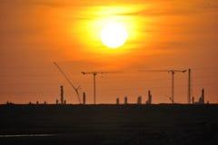 Stora kranar på den kemiska växten i solnedgången Arkivbild