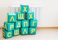Stora kuber med märker av ryskt alfabet i ett dagis Arkivbild