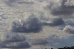 Stora mörka stackmolnmoln i den blåa himlen royaltyfria foton