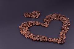 Stora och små hjärtor från kaffe i det lägre högra hörnet på en mörk bakgrund royaltyfri fotografi