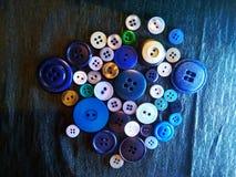 Stora och små kulöra knappar på svart arkivfoton
