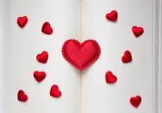 Stora och små röda hjärtor på en öppen bok Fotografering för Bildbyråer