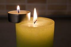 Stora och små stearinljus på mörk bakgrund Arkivfoto
