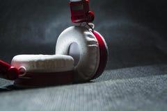 Stora och vita hörlurar för att lyssna av musik Röd plast- och hud På en svart bakgrund moderna teknologier portability arkivbilder