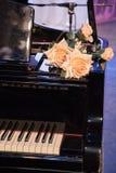 Stora orange rosor ligger på ett svart gammalt piano med tangenter på staen Arkivbilder