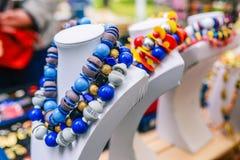 Stora pärlor på en skyltdocka Ljus kvinnlig garnering i blått och vitt Sälja färgrika halsband på räknaren royaltyfri bild
