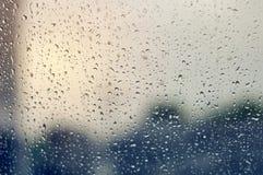 Stora regndroppar på klart exponeringsglas på en regnig molnig dag arkivfoton