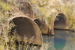 Stora rostiga metallrör under bron Arkivfoto