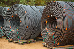 Stora rullar av rör på konstruktionsplats i skog Royaltyfri Bild