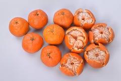 Stora runda orange mandariner på ett ljus - grå bakgrund, på vänstersidan är frukter med den hela peelen, på den högra near frukt Royaltyfri Fotografi
