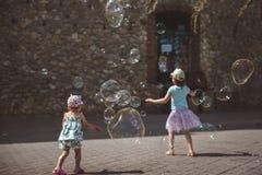 Stora s?pbubblor flyger i luftyttersidan Barn som spelar i bakgrunden i sommardag arkivbilder