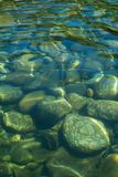 Stora släta kiselstenar skvalpar under det uppfriskande vattnet i floden royaltyfri bild