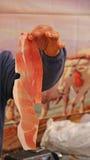 Stora slaktares hand som rymmer den stora stora biten av den rå prosciuttoen Fotografering för Bildbyråer
