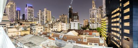 Stora stads- gemenskaper, hus i mitt av omgivet av stora högväxta byggnader arkivfoton