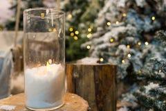 Stora stearinljus i glass vaser i snö-täckt parkerar eller en skogwh Arkivbilder