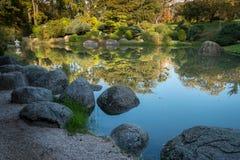 Stora stenar i ett damm Arkivfoto