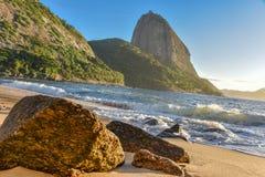 Stora stenar på den öde PraiaVermelha stranden och soluppgång med den ljusa solen som exponerar det Sugarloaf berget Fotografering för Bildbyråer