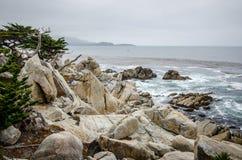 Stora stenblock längs den steniga kustlinjen av Kalifornien nära Monterey och Big Sur, på en dyster mulen dag royaltyfria foton