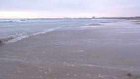Stora stormiga vågor i havet Härlig seascape med den sandiga stranden och kuststaden på bakgrund på solnedgången lager videofilmer