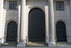 Stora svarta dörrar och vita pelare Arkivbilder