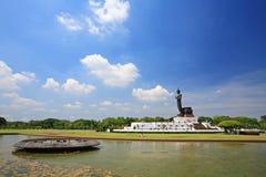 Stora svarta stående buddha med vattenreflexion arkivbild
