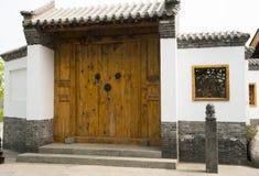 Stora trädörrar asiatKina för antik byggnad, gråa tegelplattor, vita väggar, träfönster Royaltyfri Bild