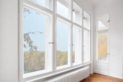 Stora träfönster i lägenhetrum av gammal byggnad arkivfoto