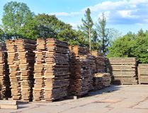 Stora träplankor som staplas i kuggar för att torka under den öppna himlen i en industriområde Tajming av trä för snickeri Manufa royaltyfria bilder