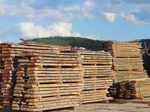 Stora träplankor som staplas i kuggar för att torka under den öppna himlen i en industriområde Tajming av trä för snickeri Manufa arkivbild