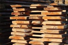 Stora träplankor som staplas i kuggar för att torka under den öppna himlen i en industriområde Tajming av trä för snickeri Manufa arkivfoton