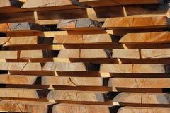 Stora träplankor som staplas i kuggar för att torka under den öppna himlen i en industriområde Tajming av trä för snickeri Manufa royaltyfri foto