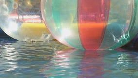 Stora uppblåsbarbollar som svävar i simbassäng arkivfilmer