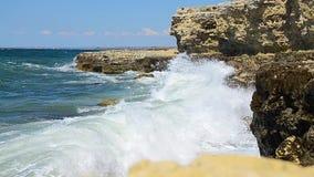 Stora vågor i stormen, bränning, kust och vaggar, plaskande vatten in i kameran, en solig vindsommardag stock video