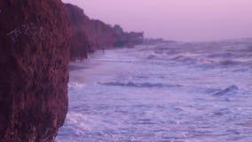 Stora vågor, med havsskum av vit färg, slår mot stranden med våt sand, lera vaggar, mot en blå himmel lager videofilmer