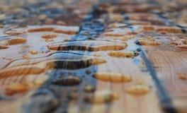 Stora vattendroppar på en trätabell royaltyfri foto