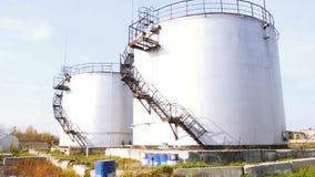 Stora vita industriella behållare för bensin och olja materiel Bränslebehållare på behållarelantgården Stora industriella olje- b Arkivfoto
