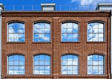 Stora Windows med en reflexion av himlen Hus i den gamla industriella fjärdedelen Kontors- och vindstillägenheter Royaltyfria Foton