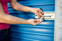 Storage: Add Lock to Unit Door. Caucasian man and woman with various props at a typical commercial storage unit Royalty Free Stock Photography