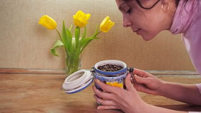 Storage of coffee beans. Ceramic container for storing coffee in the hands of a girl. A girl is smelling coffee beans in the kitch. En. Yellow tulips stock video footage