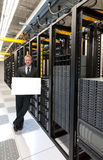 Storage Expansion. A confident datacenter manager posing by a large scale storage system with a smile Royalty Free Stock Photos