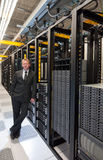 Storage Expansion. A confident datacenter manager posing by a large scale storage system with a smile Stock Images
