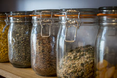 Storage jars. Labelled storage jars on shelves with rices and grains Stock Photos