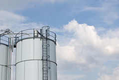 Storage Ladder with Cloudscape. Fuel storage tanks with ladder at side Stock Photos