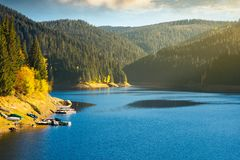 Storage lake reservoir in mountain. Beautiful autumn landscape at sunrise. pier and boats on the shore royalty free stock image